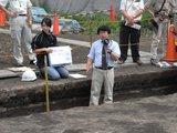 津波堆積物について説明する東北学院大学松本教授(箱尺目盛4辺りの白い層が津波堆積物)